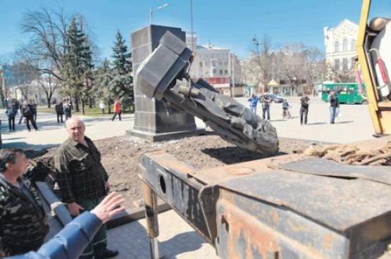 Des hommes masqués (extrême-droite) ont renversé trois statues - ici celle du révolutionnaire russe Nikolai Rudnev - dans la ville de Kharkiv. Photo Sergei Bobok/AFP.