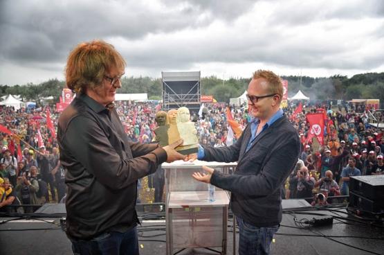 han Soete, rédacteur en chef de Solidaire, a remis le Prix Solidaire à Kristof Clerix, journaliste à Mo* magazine et Knack lors du Moment central de ManiFiesta.  (Photo Solidaire, Salim Hellalet)