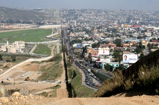 À droite, la ville de Tijuana, au Mexique, où sont installées de nombreuses usines de production qui dépendent de multinationales américaines. À gauche, les États-Unis. Entre, la frontière, sur laquelle s'érige déjà une imposante barrière. (Photo Gordon Hyde / Wikimedia)
