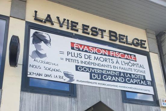 """Une banderole pour interpeler le gouvernement sur la façade de l'établissement """"La vie est belge"""". (Photo : Amin Brikci)"""