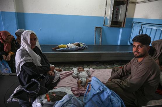 Un couple afghan change la couche de son bébé à l'aéroport. Le résultat de l'ingérence occidentale. (Photo Belga)